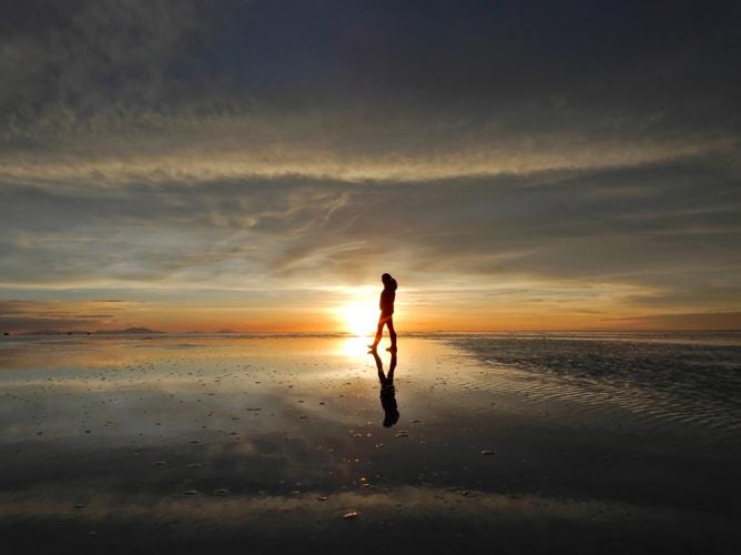 ウユニ塩湖で鏡張りのサンセットに映える人物シルエット